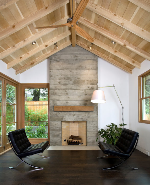 gray concrete mid-century modern fireplace with barn mantel