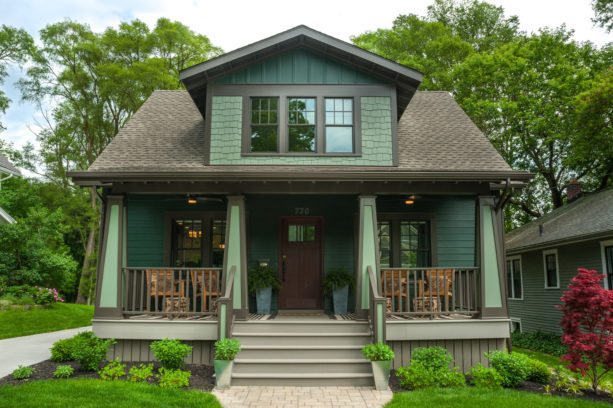 ranch style home with a mid-sized front porch in a green color