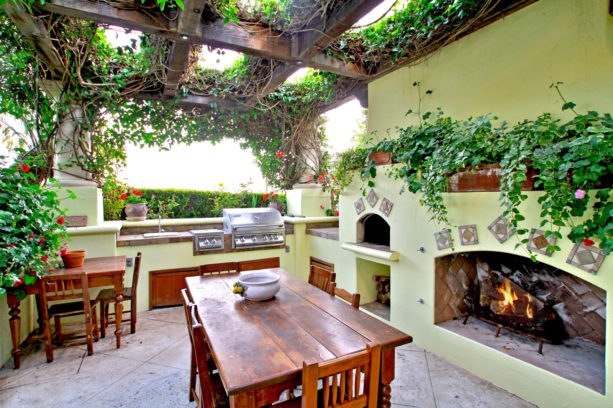 soft green outdoor fireplace with pizza oven above the wood storage