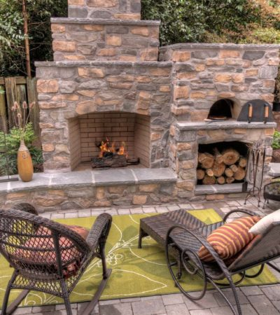 three-tiered outdoor fireplace with a wood-burning pizza oven on its side