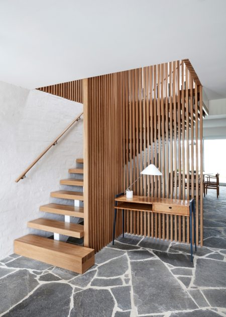 wooden staircase in an open and l-shaped design with a vertical wood slat wall