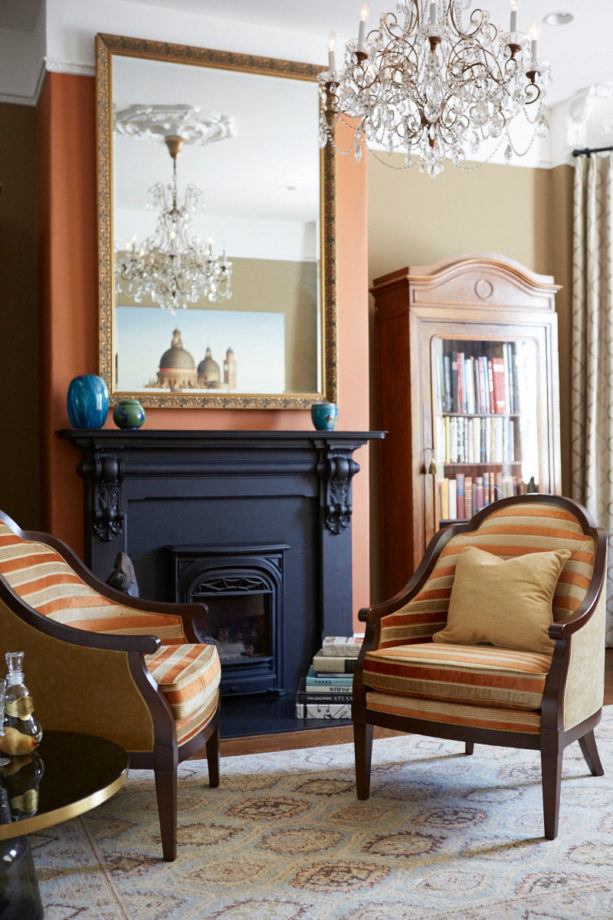 carrot orange wall and midnight blue fireplace as a focal point in a traditional living room
