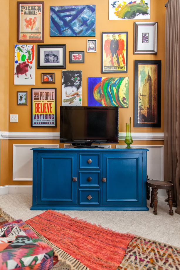 fun and eclectic living room with apricot orange wall and cobalt blue cabinet
