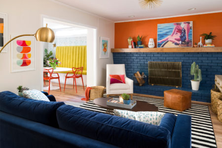 pairing of dark orange wall and navy blue brick fireplace and sofa in an eclectic living room