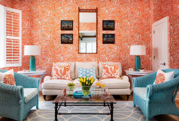 vibrant patterned orange wall combined with cyan blue accent chairs in a tropical living room